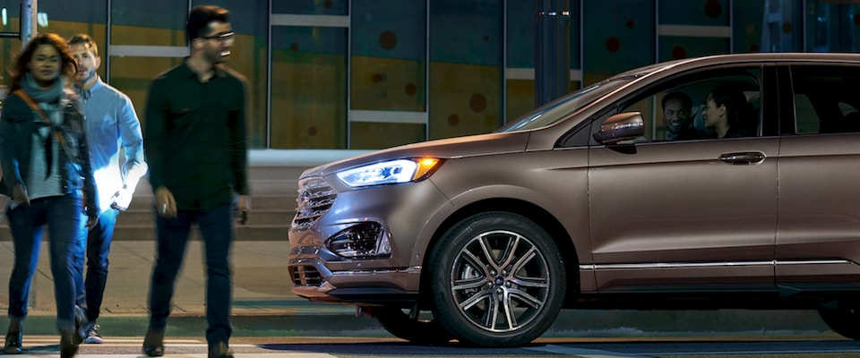 A 2019 Ford Edge stopped at a busy crosswalk