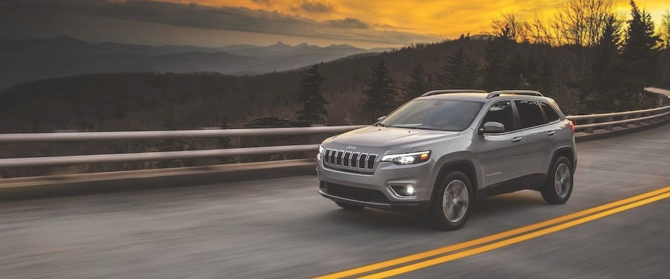 A silver 2019 Jeep Cherokee driving down a road at sunset