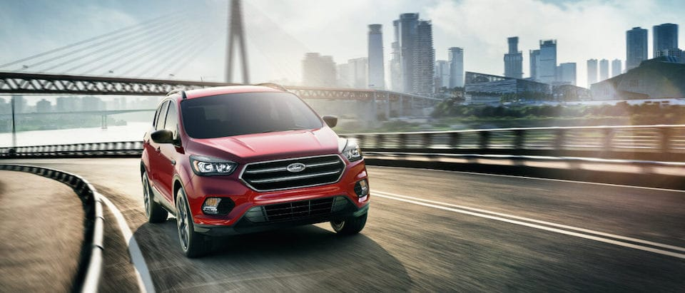 A red 2019 Ford Escape driving past a city