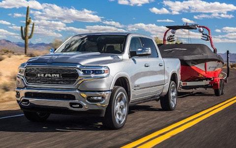 A Ram 1500 towing a boat down an open desert road