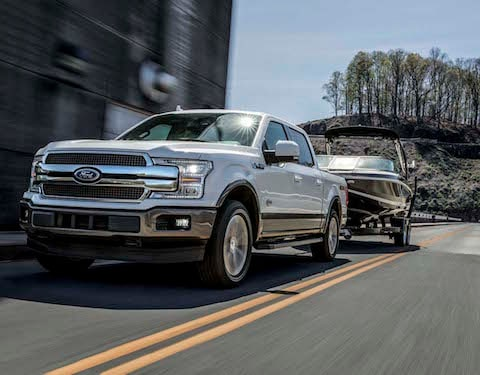 A white 2019 Ford F-150 towing a boat down an open road