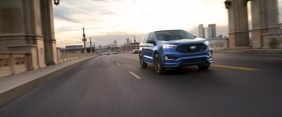A 2019 blue Ford Edge driving down  a city highway