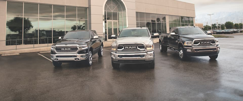 Three Ram trucks parked in front of a building