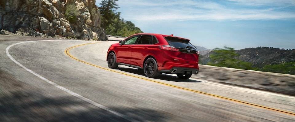 A red 2019 Ford Edge driving around a corner on a long winding road