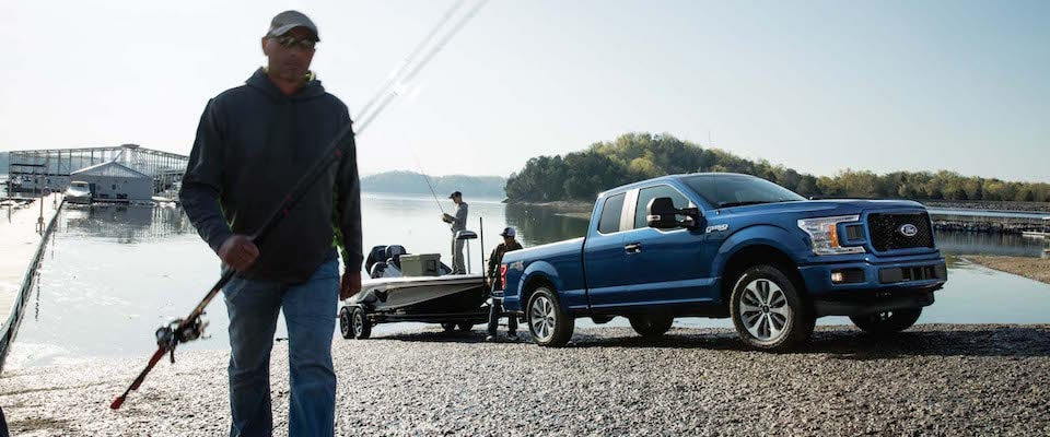 A blue 2019 Ford F-150 loading a boat into the water