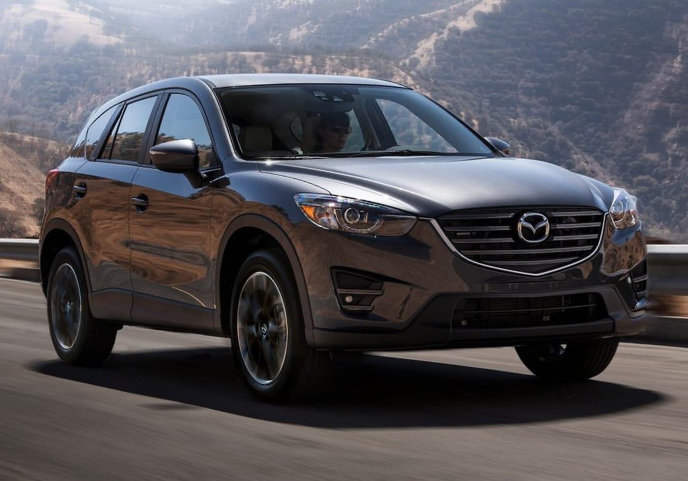 Used 2016 Mazda CX-5 driving on a mountain-side highway