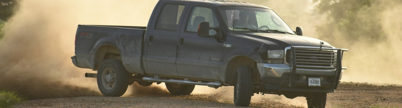 Drive side exterior of a used 4WD Ford F150 sliding sideways around a dirt road curve