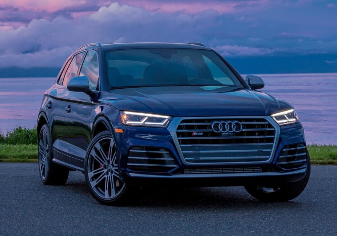 Used 2018 Audi Q5 parked by a lake at sunset with pink and orange colors in the sky reflecting off the water