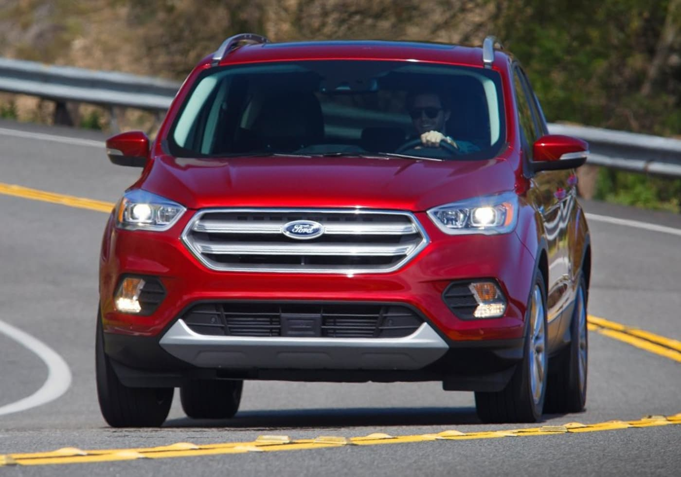 Used 2017 Ford Escape as it drives down the truck with the driver cracking a big smile