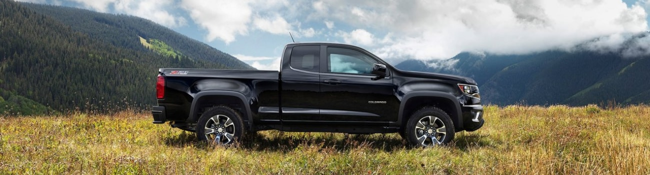 Passenger side view of a black used Chevy Colorado truck boasting great mpg ratings on a grassy knoll overlooking green mountain ranges