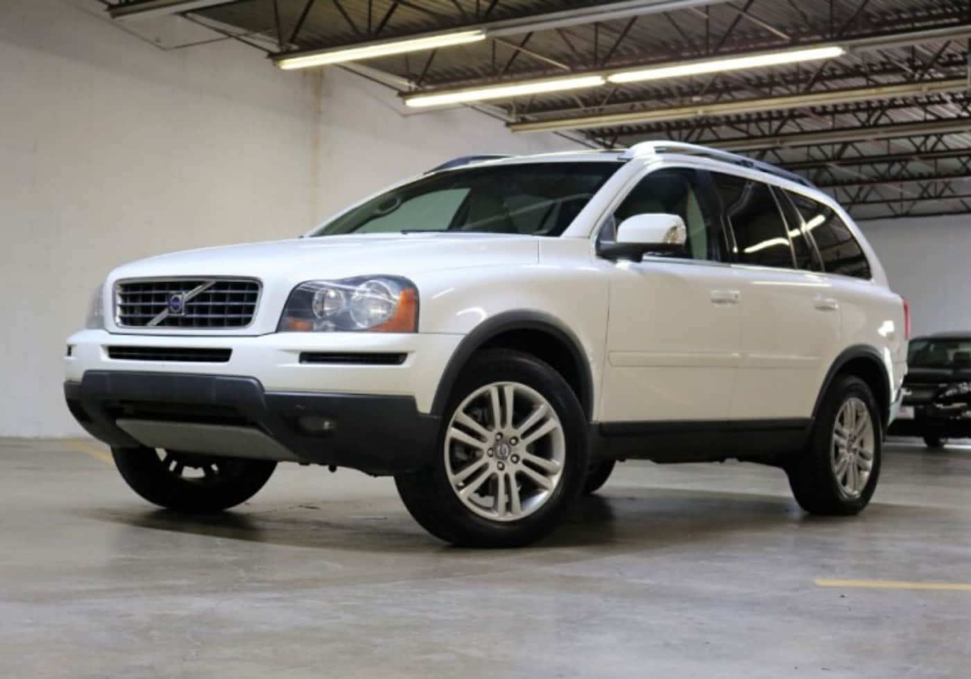 Used White Volvo XC90 SUV pulling into a parking spot inside an enclosed parking garage