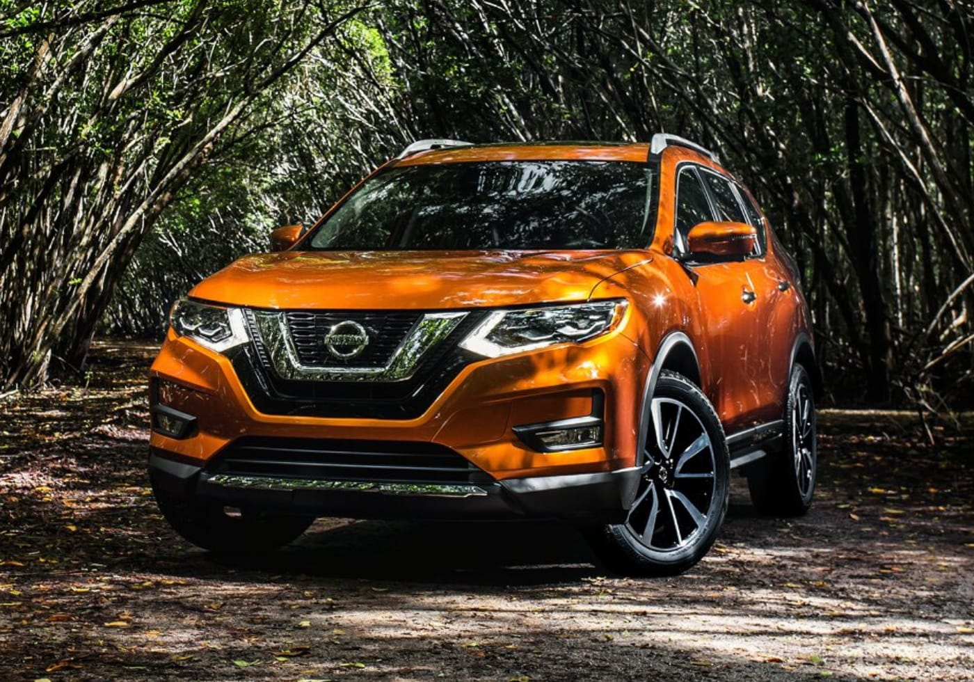 Used Orange 2018 Nissan Rogue parked on a pathway covered by large, overhanging trees grown together