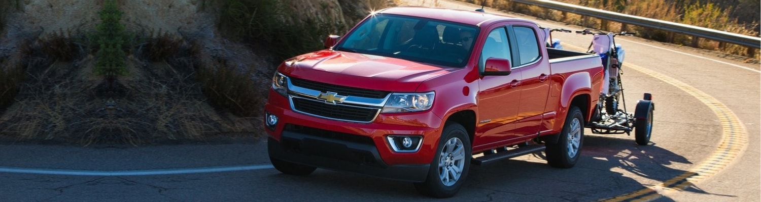 A red used Chevy Colorado truck driving around the curve or a mountain in Colorado towing motor bikes