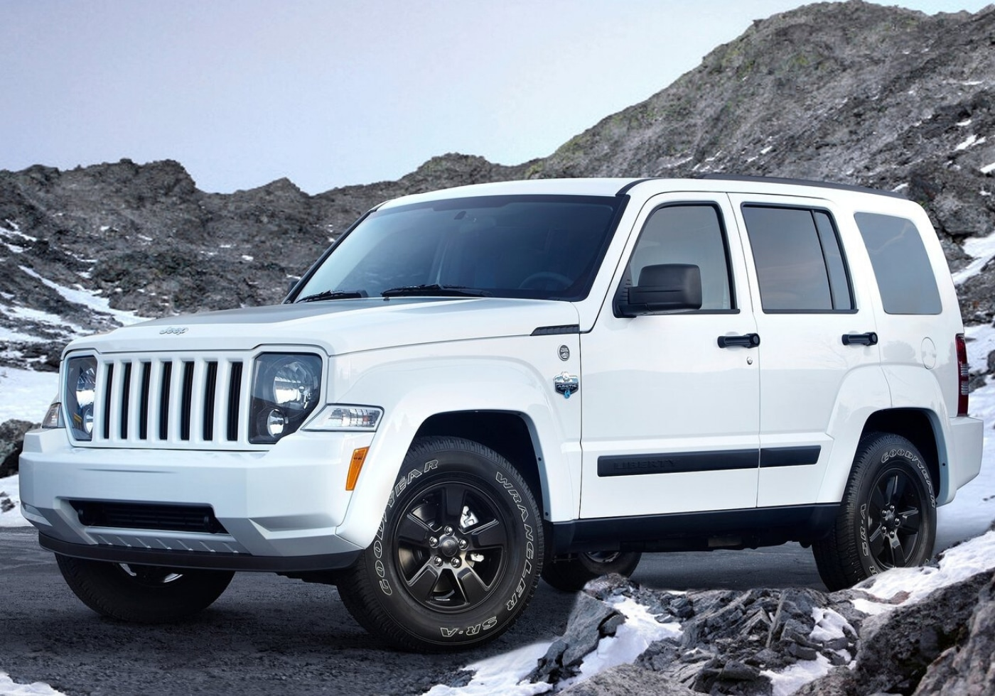 Used White 2012 Jeep Liberty Arctic Edition SUV parked by some snowy rocks with tinted windows