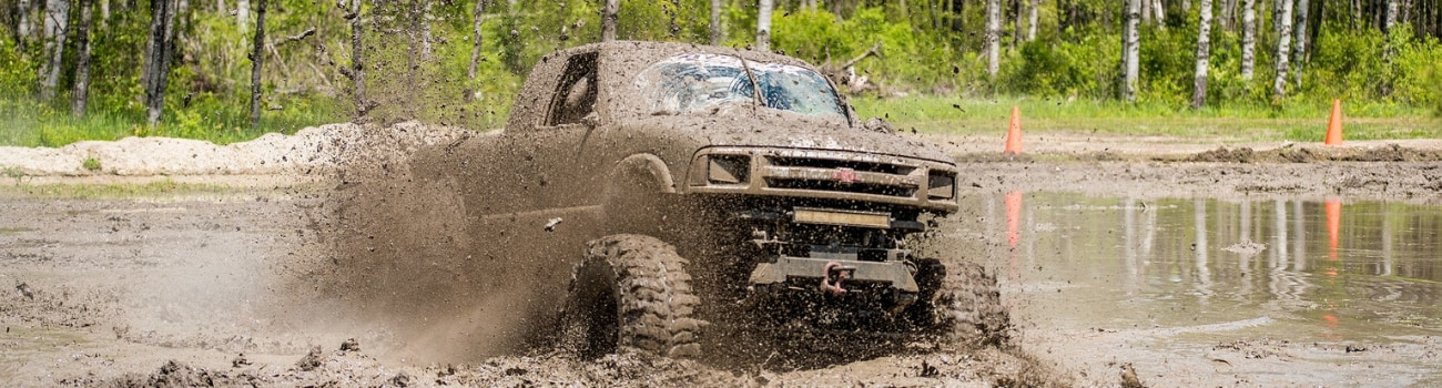 A used 4x4 Chevy truck plowing through deep mud with mud covering the entire truck