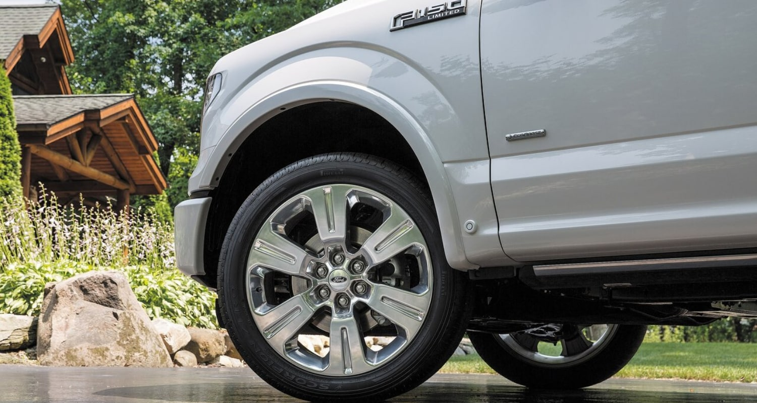 Close up view of the high quality tires, rims, and parts on a used white Ford F-150 Platinum truck