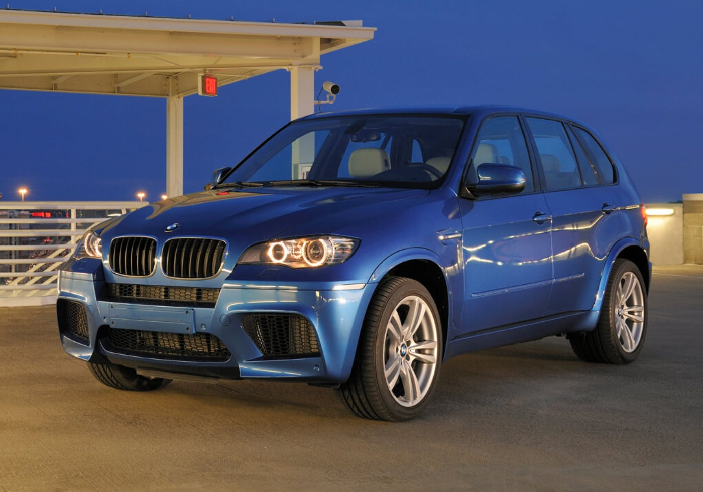 Used Blue 2010 BMW X5 parked on top of a parking building