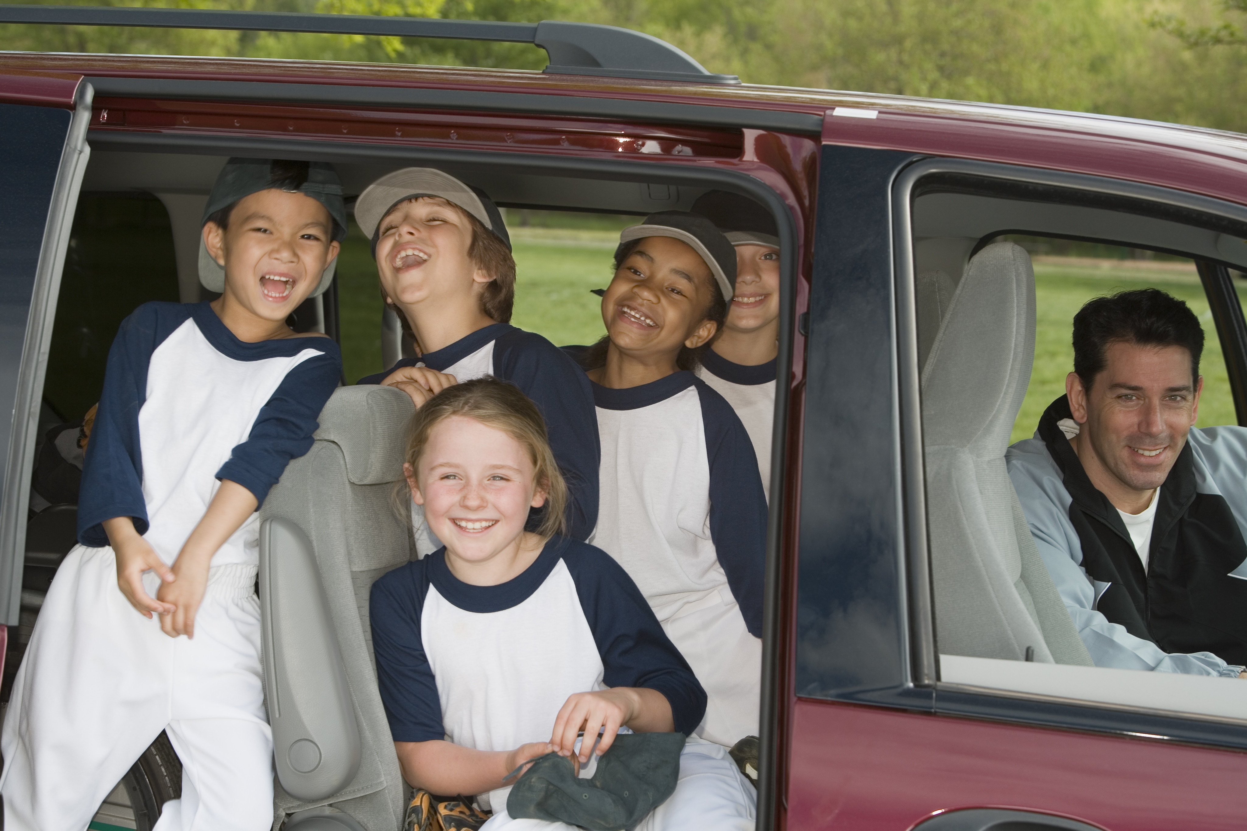 group of soccer kids sitting in a 3rd row SUV