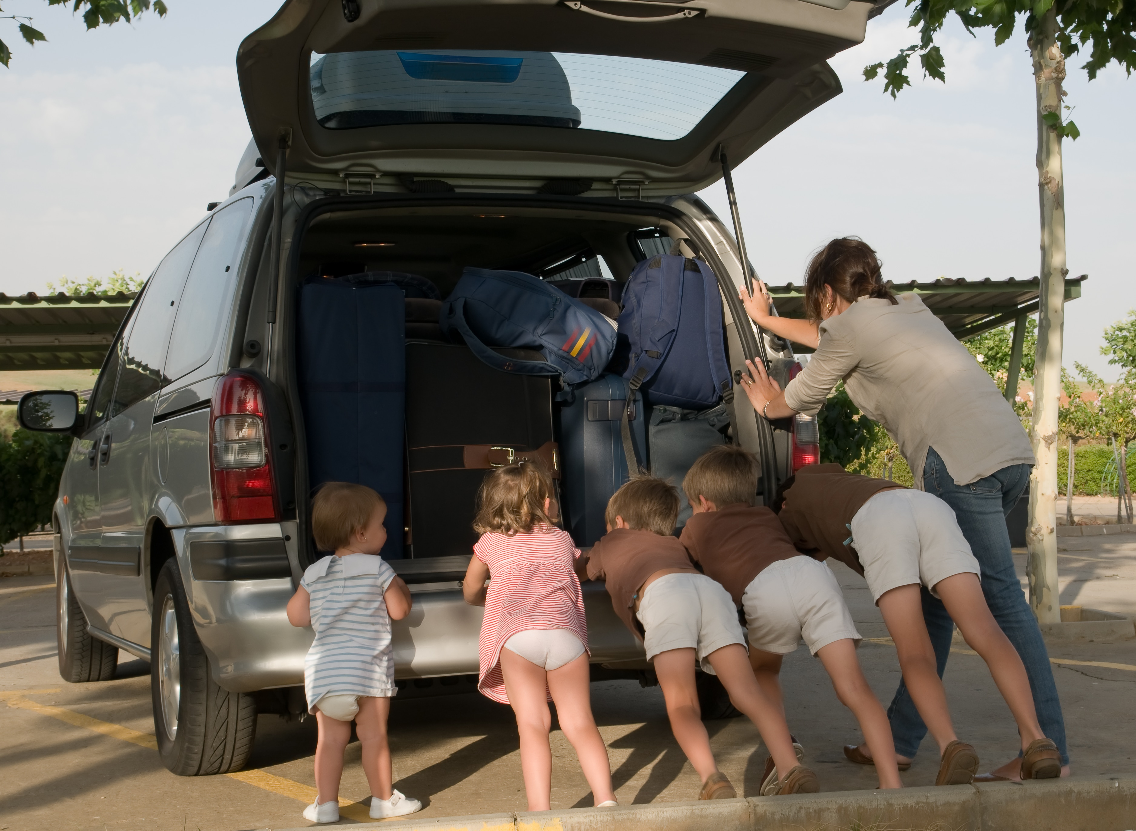 Mom and five young children push a broken down SUV