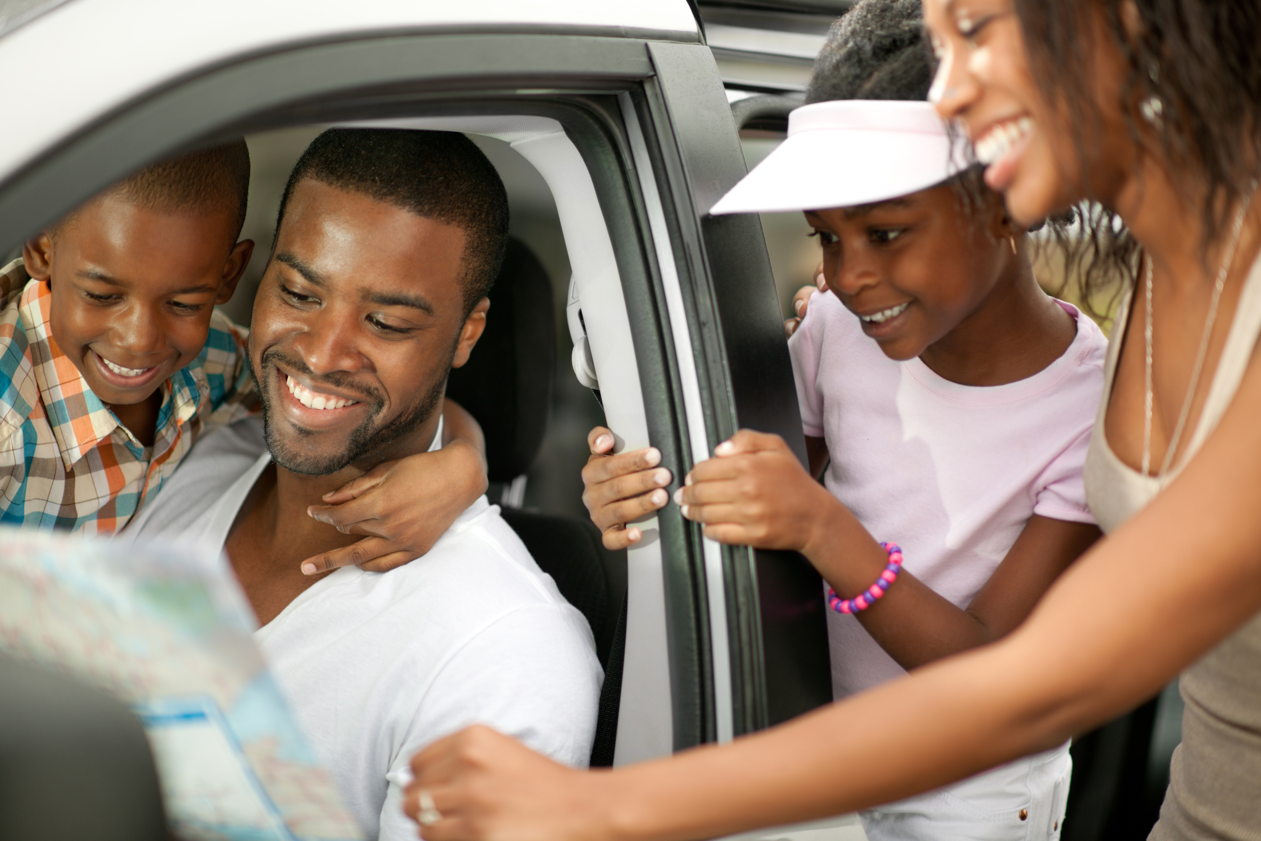 African American father smiles as he shows off his new SUV to his family