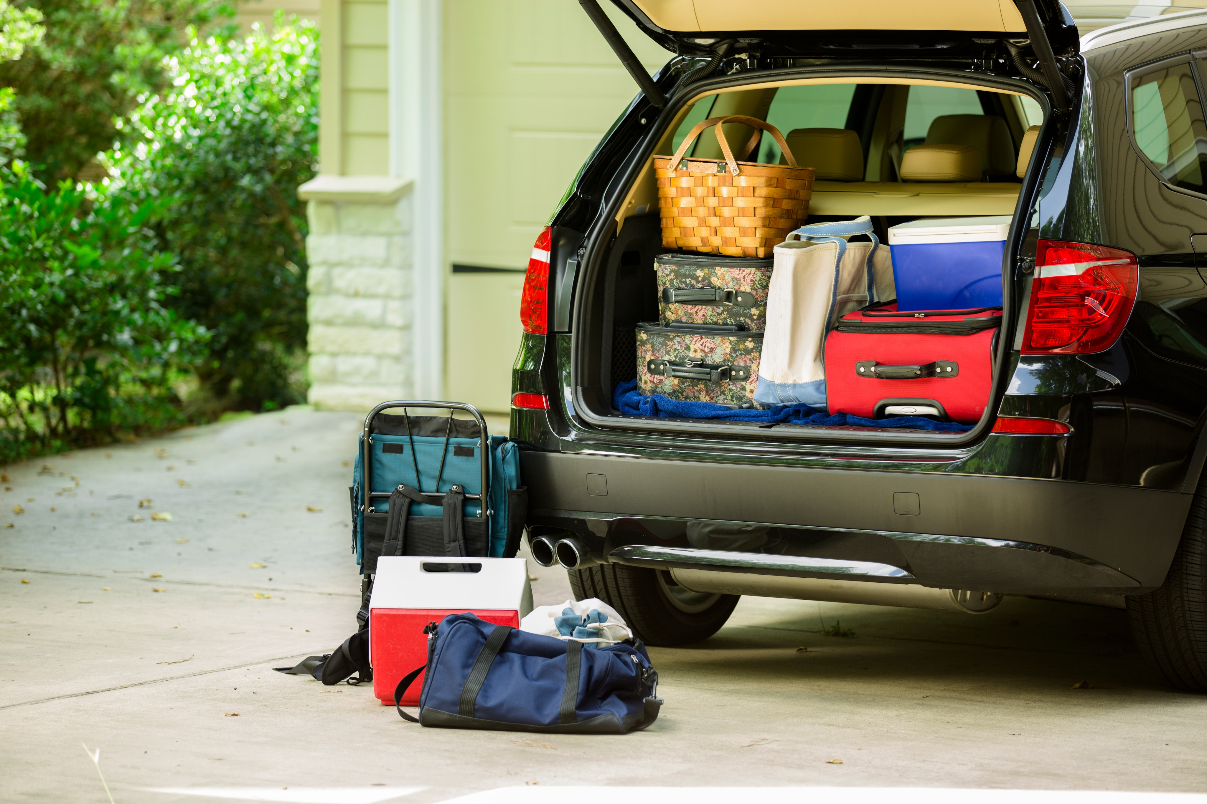SUV trunk open and packed with luggage, a picnic basket, and cooler
