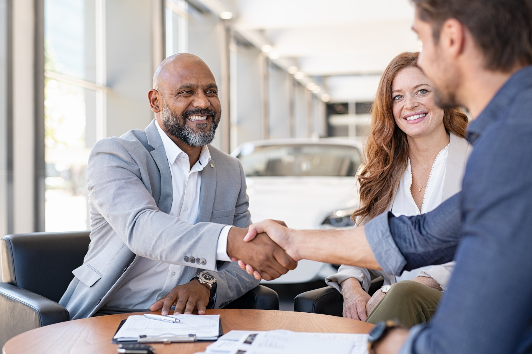 Who should I consult to get an accurate vehicle estimate at Volvo Cars New Bern of New Bern | sales agent shake shaking hand with customer