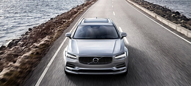 Volvo S90 driving along the water