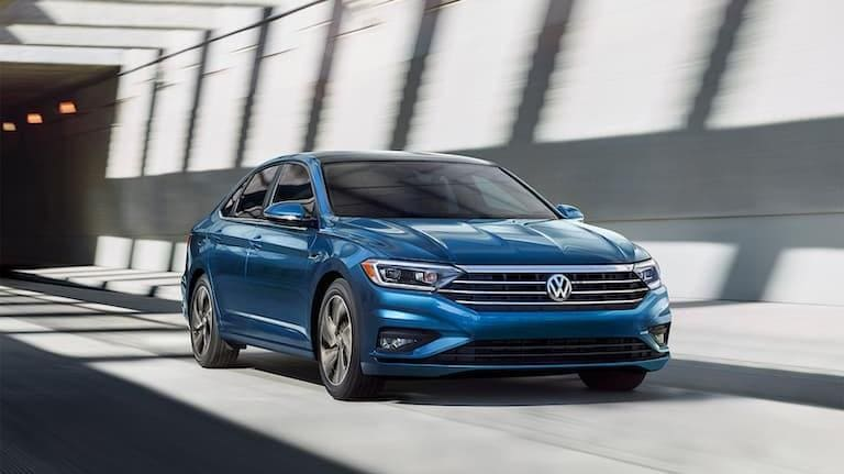 2019 Blue VW Jetta Driving under a Tunnel