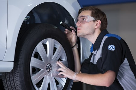 A Volkswagen technician checking out the wheel well of a VW vehicle