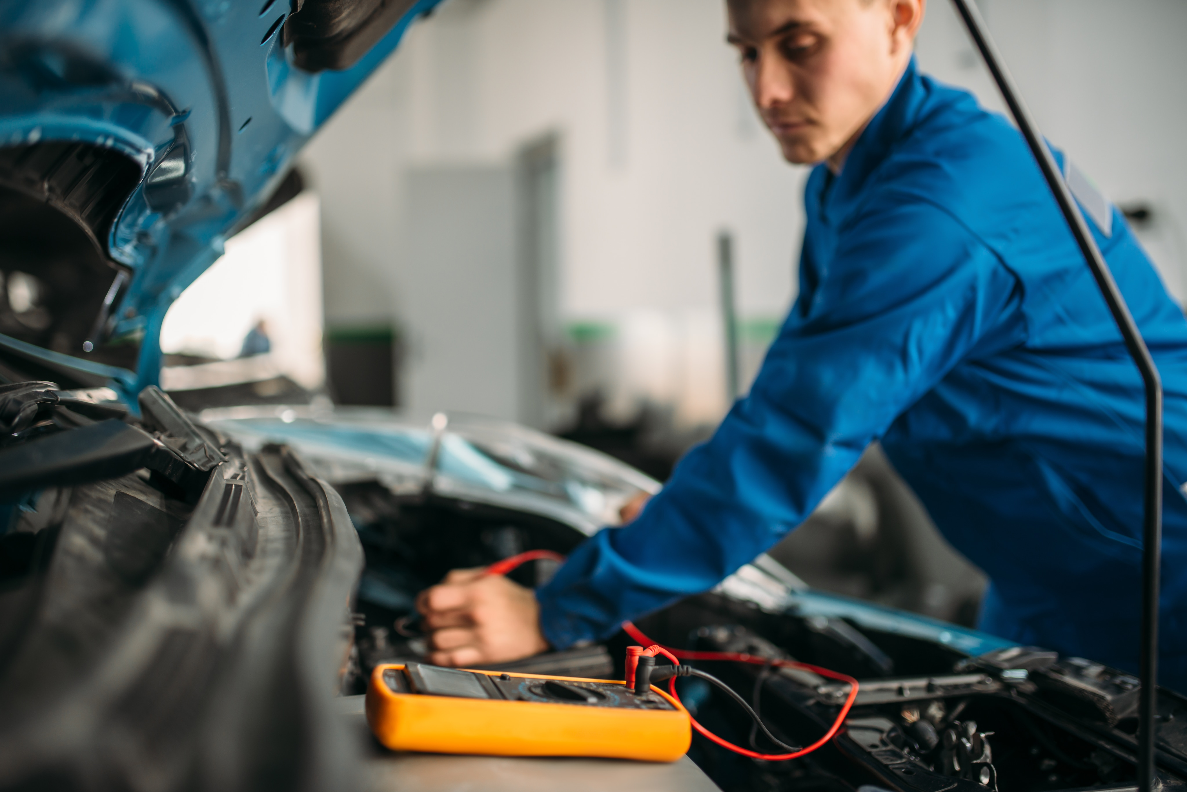 West Broad Kia is a Kia Dealership in Richmond near Laurel, VA | Mechanic working under the hood of Kia vehicle