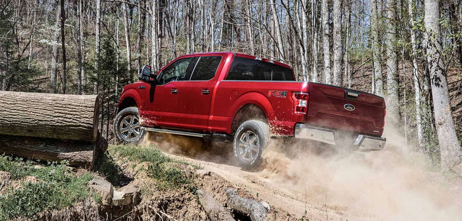 A red 2018 Ford F-150 driving up a dusty trail