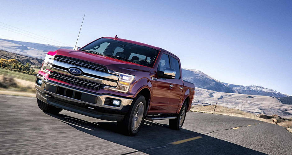 A red 2018 Ford F-150 driving towards the viewer