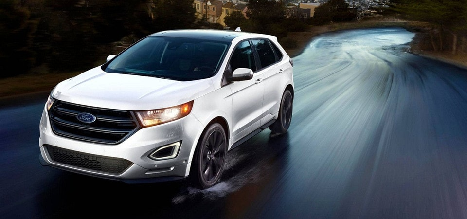 A White  Ford Edge Driving At Dusk On A Wet Road