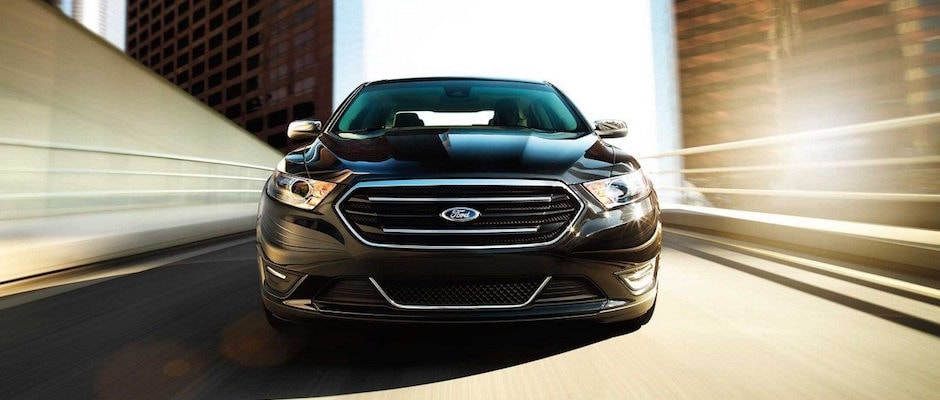 A black 2018 Ford Taurus driving down the highway