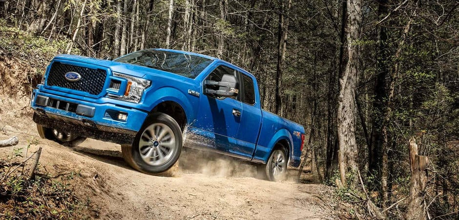 A blue 2018 Ford F-150 kicking up dust
