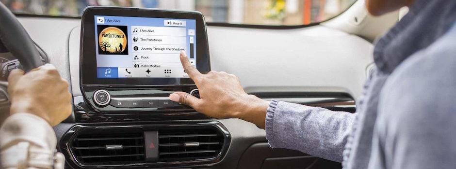 A woman putting on music through Ford SYNC