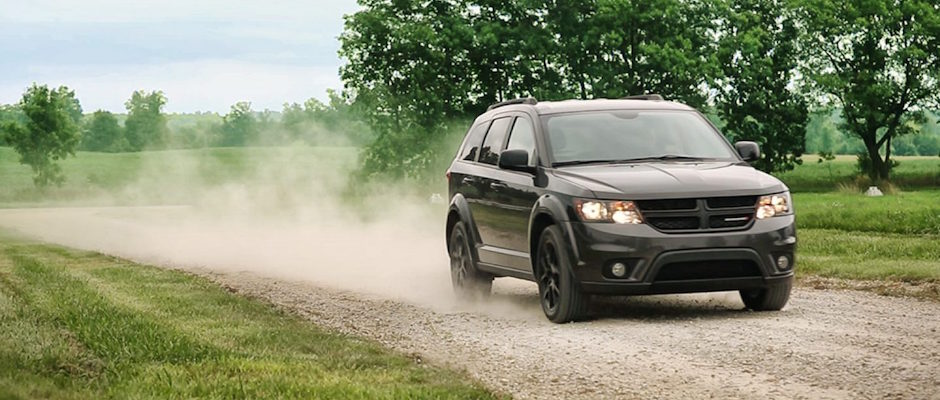 A 2018 Dodge Journey driving down a dirt road