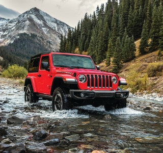 A red Jeep Wrangler driving through a stream