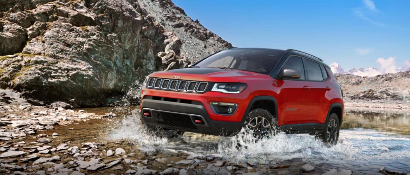 Jeep Compass driving through shallow rocky stream