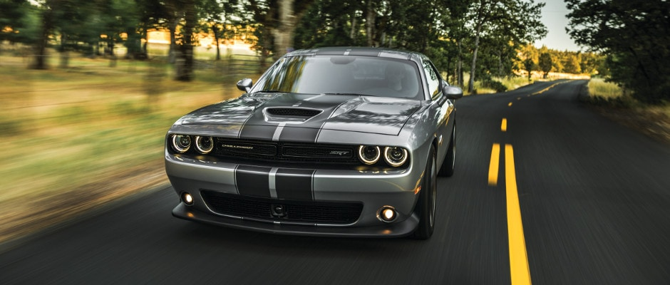 A Dodge Challenger driving down a country road
