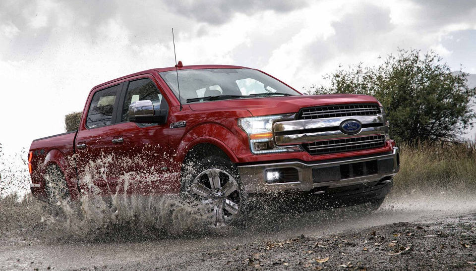 A red 2018 Ford F-150 driving through mud