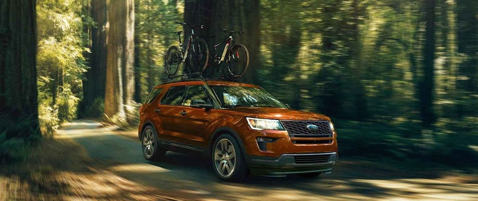 An orange 2018 Ford Explorer driving through the forest