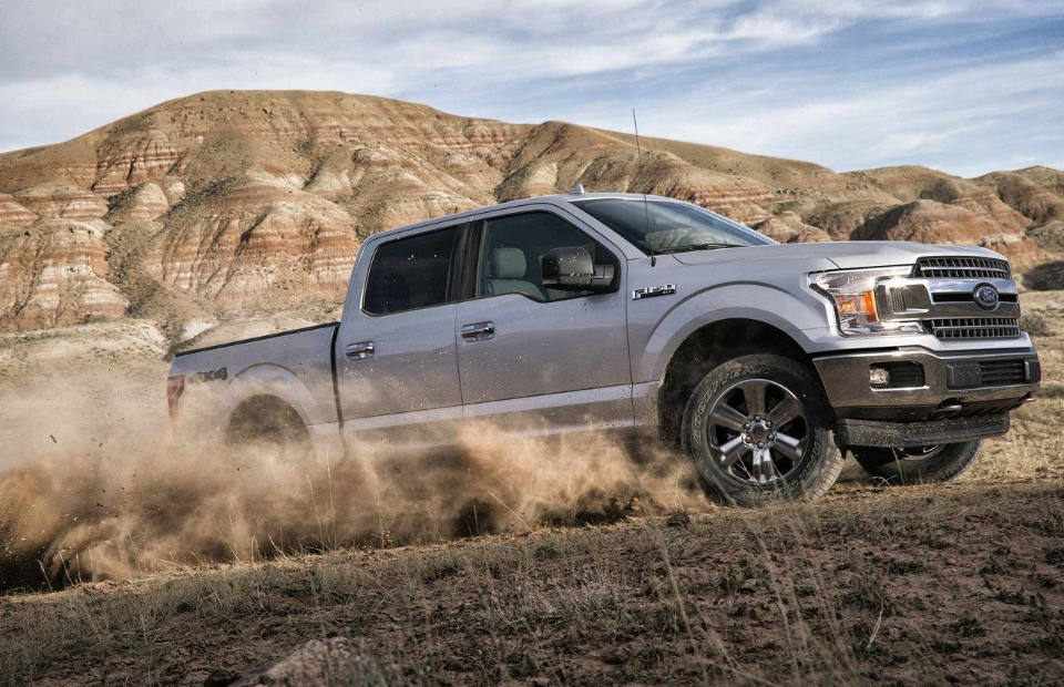 A silver 2018 Ford F-150 kicking up dust