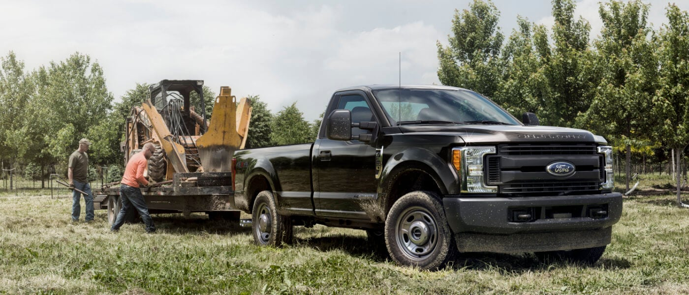 2019 Ford F-350 exterior loading construction tractor in field