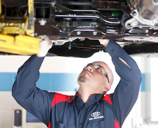 A Kia service technician changing the oil on a car