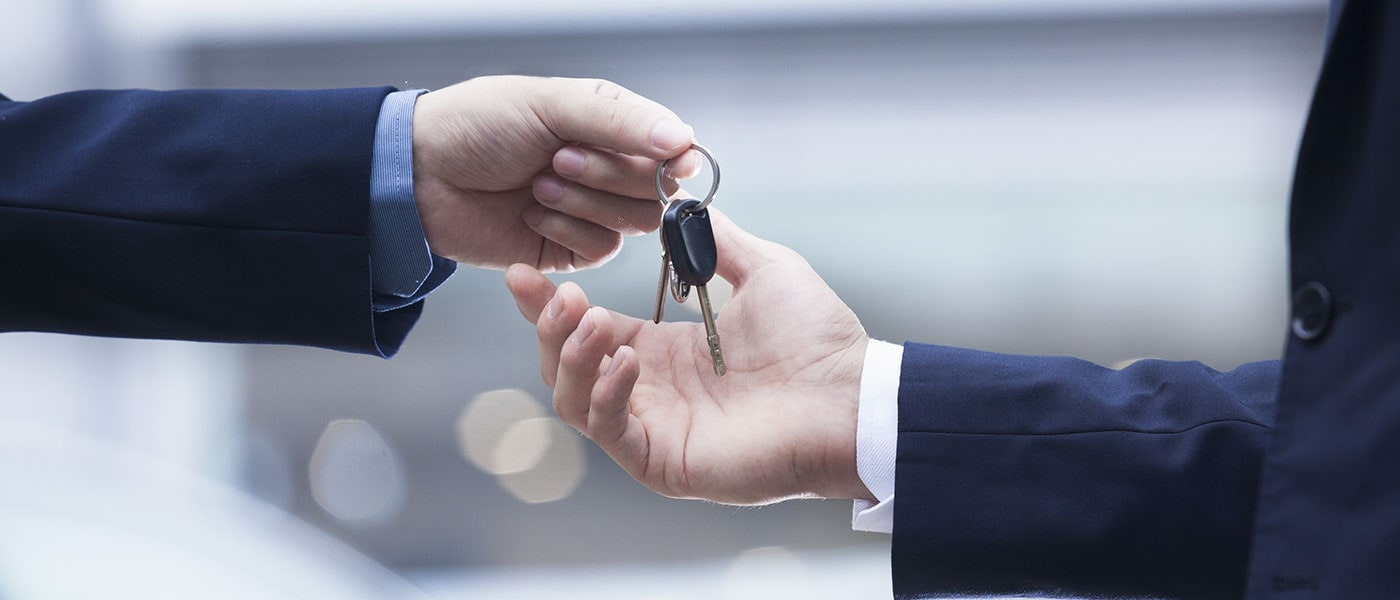 A car dealer handing keys over